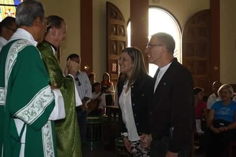 El padre Armando Rodríguez saluda al alcalde Josy Fernández y su esposa Evelin de Fernández.