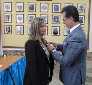 El presidente de la entidad, Juan Carlos Capllonch Calderón, entrega el Botón de Oro de la 'Orden Miguel de Cervantes y Saavedra', en su Única Clase, a Jenny C. Capllonch Calderón, presidenta de la Escuela de Deportes Acuáticos.